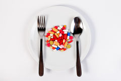 Many colored pills, capsules and syringe in a dish with a spoon and a fork. Royalty Free Stock Photos