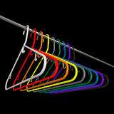 Many colored plastic coat hangers. Colored plastic coat hangers on chrome bar with black background Royalty Free Stock Photos