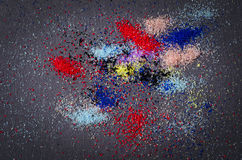 Many colored powder paint makeup artistry abstract scattered on. A black background stock photos