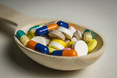 Many colored tablets in a wooden spoon on a table stock images