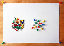 Many colored thumbtacks stuck into a white sheet of paper.     attached to  wooden board Stock Image