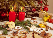 Many colorful biscuits and candles in front of christmas tree Royalty Free Stock Photography
