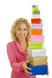 Many colorful boxes. Young blonde woman carrying many colorful gift boxes stock images