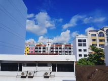 Many colorful building , green plants and TV antenna with blue sky and white clouds with copy space royalty free stock photos