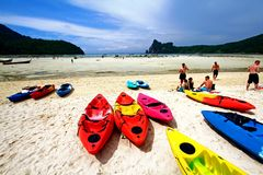 Many colorful canoe boat, people sitting and relaxing on white sand beach royalty free stock photos