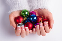 Many colorful Christmas balls in female hands. Stock Images