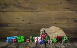 Many colorful christmas presents on wooden old background. Stock Photos