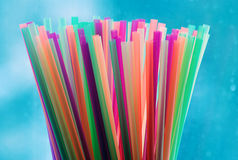 Many colorful cocktail drinking straws. On blue background with waterdrops Stock Photos