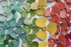 Many colorful Fan blades put on white floor or decorate on white wall background. Stock Images