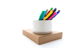 Many colorful felt tip pens on Brown paper box. Isolated on white royalty free stock photography