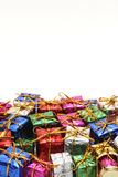 Many colorful gift boxes with gold ribbons on white background. Royalty Free Stock Images