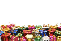 Many colorful gift boxes with gold ribbons on white background. Stock Photos
