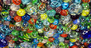 Many colorful glass marbles with smiley light reflection Stock Images