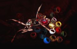 Many colorful glass rings and neklace on a dark red cloth. Close up Stock Image