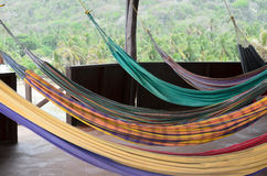 Many colorful hammocks hanging at veranda in tropics royalty free stock images