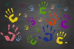 Many colorful hand prints. Many different colorful hand prints on a blackboard stock images
