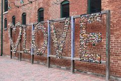 Colorful hanging locks on a love fence with a red wall in background in Toronto in the Distillery District in Canada. Many colorful hanging locks on a love fence royalty free stock images