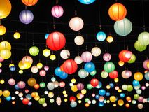 Many colorful and illuminated round chinese paper lanterns hanging in the black sky royalty free stock photos