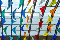 Many colorful kites against the glass roof stock photos