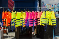 Many colorful life jacket or life vest hanging on a clothesline.  stock image