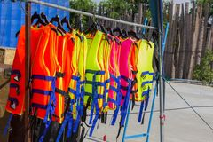 Many colorful life jacket or life vest hanging on a clothesline.  stock photography