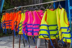 Many colorful life jacket or life vest hanging on a clothesline.  royalty free stock photo