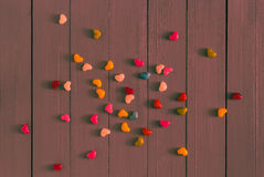 Many colorful little hearts wooden background stock photography