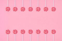 Many colorful lollipop candys arranged in two group and empty space in the center on pink background stock photos