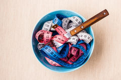 Many colorful measuring tapes in bowl on table Stock Images