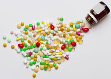 Many colorful medicines spilling out of a bottle. Royalty Free Stock Photos