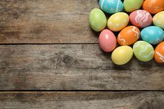 Many colorful painted Easter eggs on wooden background, top view. Space for text royalty free stock photos