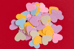 Many colorful paper heart shaped confetti on pink or red background. Valentine`s concept card stock photography