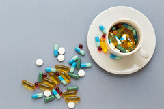 Many colorful pills in cup on gray background Royalty Free Stock Photography