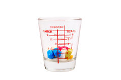 Many colorful pills in a measuring cup of glass. Stock Images