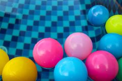 Many colorful plastic balls floating in pool Stock Photo