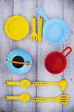 Many colorful plastic toy dishware on lilac wood Stock Image
