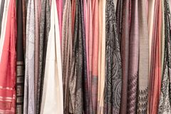 Many colorful scarves hanging for sale at market. Colorful background Stock Image
