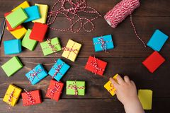 Many colorful small gift boxes with kids hand to take one box Stock Images