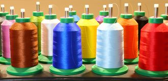 Many colorful spools of thread in dressmaking factory Stock Image