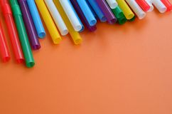 Many colorful straws for drinks lies on a bright orange backgrou. Nd surface Royalty Free Stock Photos