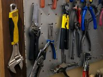 Many colorful tools on the stand in the workshop stock images