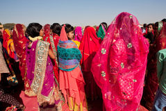 Many colorful women in sari standing in crowd. JAISALMER, INDIA - MAR 1: Many colorful women in sari standing in crowd before the presentation on the Desert Royalty Free Stock Images