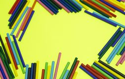 Many colorful wood sticks lays yellow background. stock photo