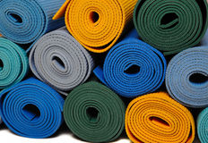 Many colorfull yoga mats as a background. Isolated on white background Royalty Free Stock Photos