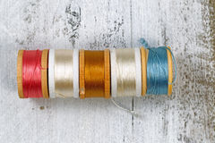 Many colors of thread within their spools Stock Photo