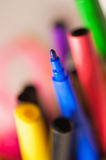Many coloured felt tip standing in a box. Selective focus on a blue tip with motion blur effect backgrounds royalty free stock image