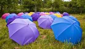 Many coloured open umbrellas. Lot's of colourful open umbrellas in a farmers grass field Stock Photos