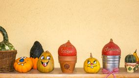 Many coloured pumpkins with and without face. Before a yellow wall stock images