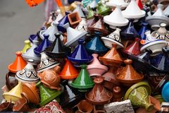 Many coloured tajines for sale in a street, background stock image