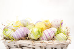 Many colourful easter eggs in basket Stock Photo